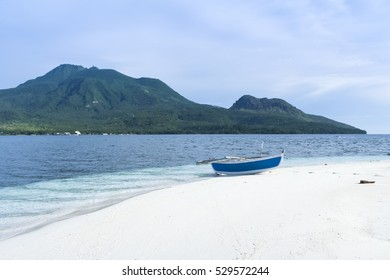 traditional banka outrigger canoe on white beach camiguin island, mindanao in the philippines, with volcano in the background