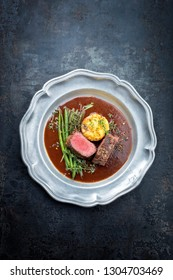 Traditional barbecue aged venison backstrap roast with green beans, fried mashed potatoes and herbs in brown red wine sauce as top view on a pewter plate with copy space