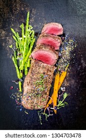 Traditional barbecue aged venison backstrap roast with green asparagus, carrots and herbs as top view on a rustic metal sheet
