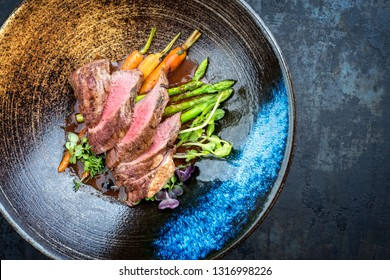 Traditional barbecue aged venison backstrap roast with green asparagus, carrots and herbs in brown red wine sauce as top view on a modern design bowl with copy space right