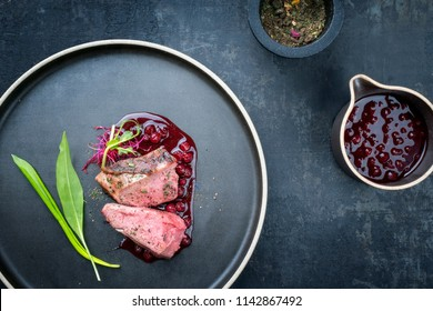 Traditional barbecue dry aged sliced venison fillet steak with wild garlic and cowberry sauce as top view on a plate with copy space