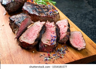 Traditional barbecue dry aged sliced wagyu sirloin beef steak with spice and herbs as closeup on modern design wooden cutting board