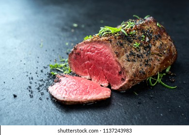 Traditional barbecue dry aged wagyu fillet steak with herb and spice marinated as closeup on a black board