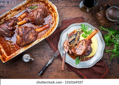 Traditional barbecue leg of lamb with eggplants and mashed potatoes in tomato red wine sauce as top view on a pewter plate and stewpot