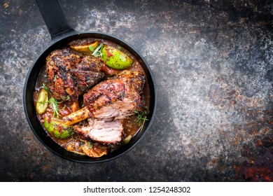Traditional barbecue leg of lamb with lemon and tomatoes as top view in a cast-iron skillet with copy space right