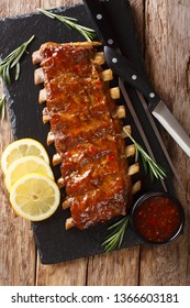 Traditional barbecue pork ribs served with spicy sauce and lemon close-up on a wooden table. Vertical top view from above