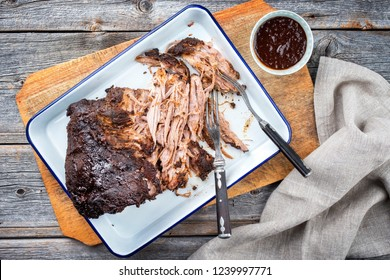 Traditional barbecue pulled pork piece of Bosten butt torn to bits as top view on a board
