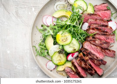 Traditional barbecue skirt steak sliced with salad and avocado as close-up on a plate with copy space right