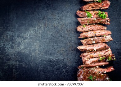 Traditional barbecue skirt steak sliced as close-up on a knife with copy space left