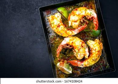 Barbecue traditionnel queue de homard épineux coupée en tranches et offerte avec sauce au citron safran en vue de dessus sur un plateau de métal avec place pour copie laissée