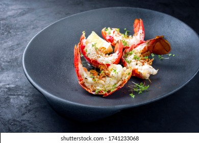 Traditional barbecue spiny lobster tail sliced and offered with lemon slice and herbs as closeup on a modern design plate