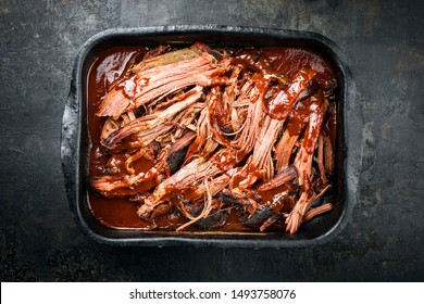 Traditional barbecue wagyu torn to bits pulled beef in hot chili sauce in a roasting dish as top view on a rustic board with copy space
