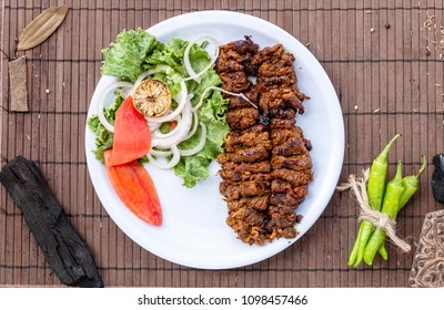 A traditional barbeque dish bihari kabab in a white plate along vegetables on a wooden table top view