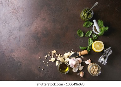 Traditional Basil pesto sauce in glass jar with ingredients above fresh basil, olive oil, parmesan cheese, garlic, pine nuts, lemon over dark texture background. Top view, space