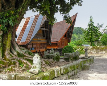 Traditional Batak houses in Ambarita with stone chairs used for judgement and executions, Samosir island, Sumatra, Indonesia