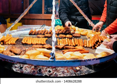 Traditional BBQ barbeque wurst sausages on Christmas market in Germany in Europe in winter. German Night street Xmas and holiday fair in European city. Alexanderplatz in Berlin