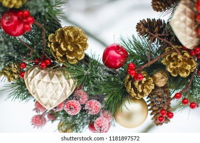 traditional beautiful Christmas wreath decoration for the new year for the holiday. Made of pine, apples, cones, red berries, Christmas toys. All against the background of snow.