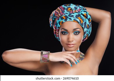 Traditional beauty. Beautiful African woman in headscarf and jewelry posing against black background and looking at camera