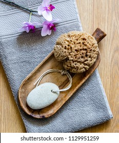 traditional beauty and body care objects with orchid flowers over grey towel for minimalist home spa and healthy bath, top view