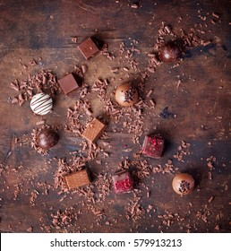 Traditional Belgian chocolate variety over rustic wooden board, decorated with chocolate swirls. Top view