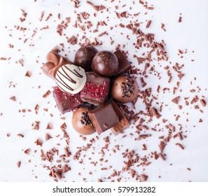 Traditional Belgian chocolate variety over white marble board, decorated with chocolate swirls. Top view