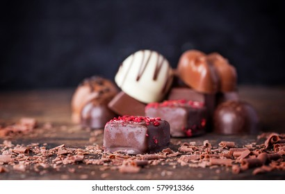 Traditional Belgian chocolate variety over rustic wooden board, decorated with chocolate swirls.