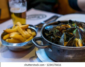 Traditional belgian food, mussels cooked and served in a metal pot and french fires, with beer in a restaurant, Brussels, Belgium
