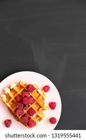 Traditional belgian waffle with raspberries on pink plate over black background, top view. Flat lay, overhead, from above. Copy space.