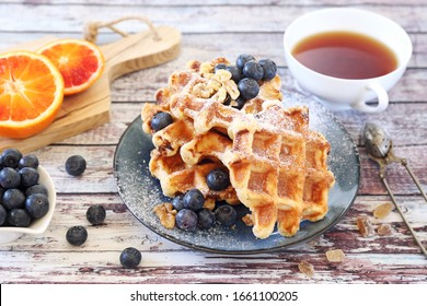 Traditional belgian waffles with blueberries, blood oranges and cup of black tea for breakfast