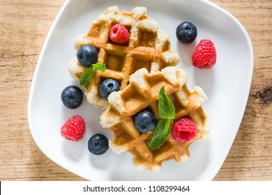 Traditional belgian waffles with blueberries and raspberries on wooden table. Top view