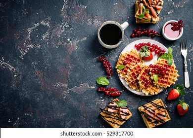 Traditional Belgian waffles in the plate with fresh berries, fruit and chocolate sauce and coffee , top view with copy space