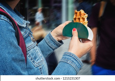 Traditional belgian wafle in woman's hands on a street