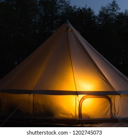 Traditional bell tent glows at night at forest