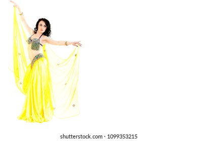 Traditional belly dance performed by young attractive natural beauty woman dressed in colorful wear with long curved dark hair. Isolated on abstract white background with clipping path. Space for text