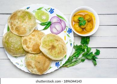 Traditional Bengali cuisine - Green peas kachori or Koraishutir kochuri in a ceramic plate along with a bowl of Spicy dum aloo curry, onion, lemon and green chilli salad. - Shutterstock ID 1896344143