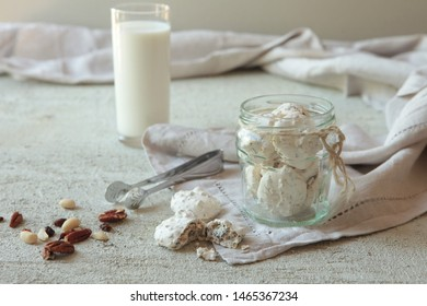 Traditional Beze or Meringues with nuts in a glass jar on concrete background. Copy space. A glass of milk. Homemade Meringue made with love.