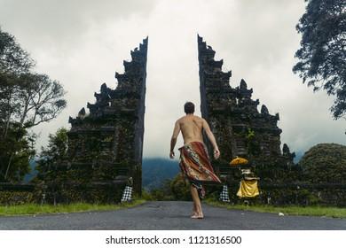 Traditional big gate entrance to temple man entering. Bali Hindu temple. Bali island, Indonesia.