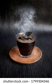 Traditional Black Coffee Kopi Jos with Hot  Charcoal Inside on Wooden Plate