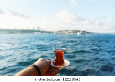 Traditional black Turkish tea in a glass on a plate in the hands of a man with a view of the Bosporus and Istanbul background. Travel to Turkey. Soft focus and beautiful bokeh.