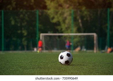 Traditional black and white soccer ball on green grass playground. Football game, Outdoors activity, summer sunny day.