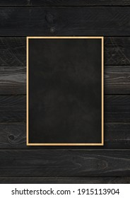 Traditional blackboard isolated on a black wood background. Blank vertical mockup template