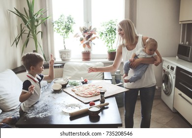 Traditional blond family with two sons in a real cozy kitchen prepare pizza, joke and throw flour, emotional life style, selective focus and toning