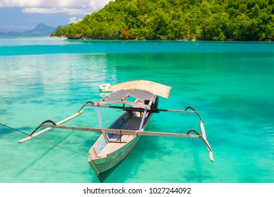 Traditional boat floating on the transparent blue toned lagoon of the remote Togean (or Togian) Islands, Central Sulawesi, Indonesia, upgrowing travel destination for young hipsters.