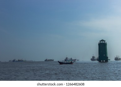 Traditional boat with lighthouse and background of ships under blue sky, North Jakarta, Indonesia