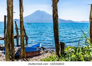 Traditional boat on beach at Lake Atitlan with Atitlan & Toliman volcanoes on horizon, Guatemala, Central America
