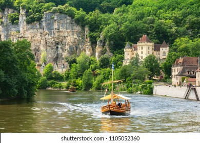 Traditional boat on Dordogne river with the Village of La Roque Gageac in the background. Village located in Dordogne department in France.