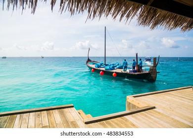 Traditional boat on tropical beach on Maldives. Sunrise cruise yacht.