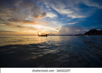 Traditional boat on waves at sunset beach