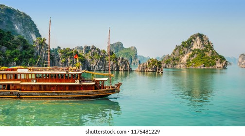 Traditional boat sailing in the green waters among the rock islands of Halang Bay Vietnam
