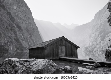 Traditional boathouse at lake Obersee in alpine landscape on a summer morning. Black and white image of a famous travel destination in Schönau am Königssee, Bavaria, Germany.
